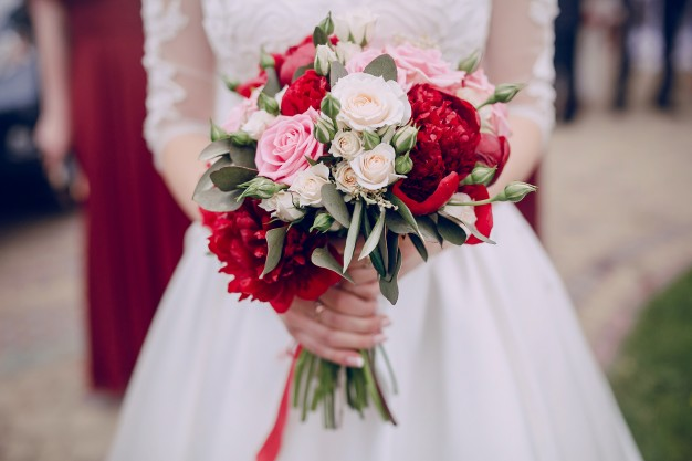 close-up-hands-holding-wedding-bouquet_1157-319-freepik